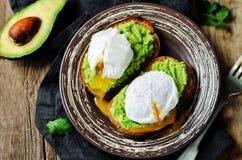 Kłusować jajeczne Avocado żyta grzanki Zdjęcia Stock
