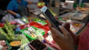 4K、亚洲女性手举行和屏幕智能手机在传统市场上 影视素材