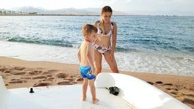 4k一点小孩男孩身分录影在筏的在海海滩 影视素材