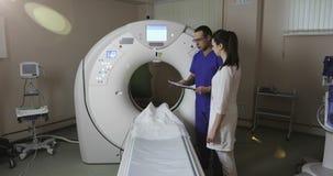 4K两医生在CT扫描屋子谈论耐心` s病史在一家新的现代癌症治疗医院 影视素材