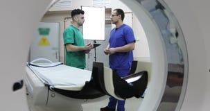 4K两年轻医生谈论患者的治疗在屋子里与CT扫描器 股票录像