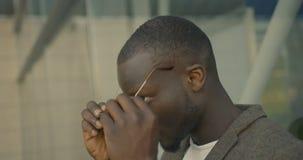 4k严肃的时兴的非洲人的英尺长度投入在他的太阳镜的衣服的在街道 影视素材