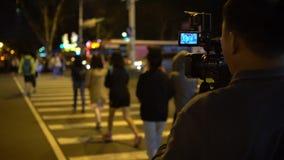 4K亚裔操作员与摄像头记录的步行者交叉路夜 股票录像