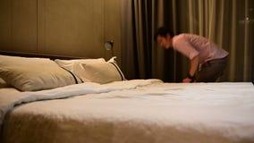 4K亚裔旅游人走入酒店房间和跳在床上在成功的旅行旅途以后 股票视频