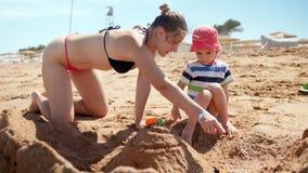 4k使用与她的小孩儿子的年轻母亲慢动作录影,当放松在含沙海海滩时 股票视频