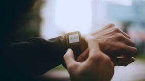 4K使用聪明的手表定时器的运动员在开始前 供以人员看smartwatch跟踪仪定时器设置运行时间 股票视频