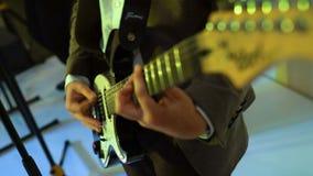 4k吉他弹奏者弹在夜总会阶段,颜色光闪光的声学吉他  股票视频