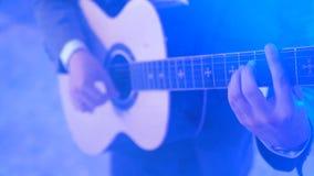4k吉他弹奏者弹在夜总会阶段,颜色光闪光的声学吉他