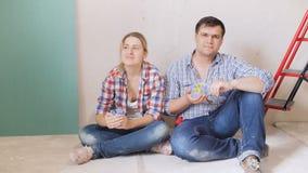 4k和放松坐他们的新房地板的愉快的年轻夫妇英尺长度在整修下 股票录像