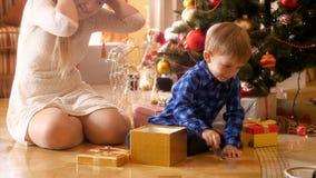 4k坐在圣诞树下和采取玩具的愉快的笑的小男孩英尺长度在礼物盒外面 股票视频