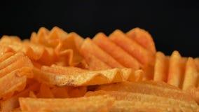 4K堆英尺长度被吹奏的土豆片用香料喜欢辣椒粉或辣椒,转动在黑背景,低速 股票视频