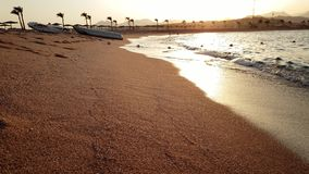 4k完善的海滩美好的录影与金黄沙子的在日落 镇静波浪和发光的太阳在水表面 股票录像