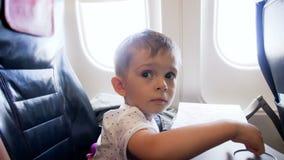 4k小小孩男孩录影坐在飞机的乘客座位在飞行期间 股票录像