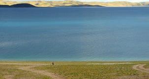 4k巨大的云彩滚动在湖namtso的,走在湖边的西藏人 股票录像