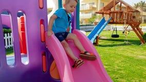 4k快乐的微笑的小孩男孩骑马英尺长度在幻灯片的在儿童操场在公园 股票录像