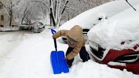 4k愉快的微笑的小孩男孩开掘的随风飘飞的雪英尺长度在汽车停车处的与大雪铁锹 股票视频