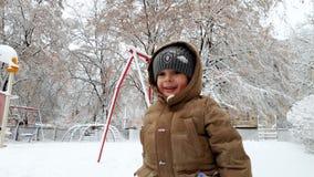 4k愉快的微笑的小孩男孩投掷的雪球录影在操场的在雪风暴以后的冬天公园的 股票录像