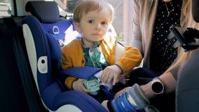 4k投入她的孩子的妇女英尺长度chidlren汽车安全位子 安全和保护在运输 股票录像