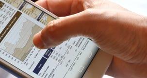 4k浏览在智能手机的商人财务新闻,手指感人的财务圆图 股票录像