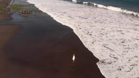 4K白色礼服的走在黑火山的海滩,巴厘岛的少妇空中飞行英尺长度  股票视频