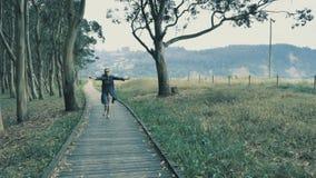 4k相当走在自然木指挥台的女孩在有青山的美丽的自然树丛里在 股票视频