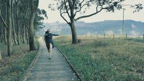4k相当走在自然木指挥台的女孩在有青山的美丽的自然树丛里在 影视素材