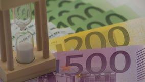 4K移动式摄影车滑有不同的价值欧元钞票的沙子滴漏  股票视频