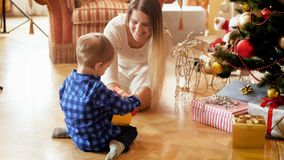 4k给她的3岁的愉快的年轻母亲英尺长度小孩男孩在箱子的圣诞节礼物在早晨 影视素材