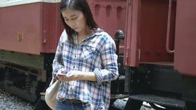 4k英尺长度 亚洲旅游妇女旅行乘火车到达火车站并且打电话 股票视频