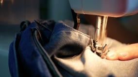 4k英尺长度 关闭缝合有一台缝纫机的妇女蓝色牛仔布牛仔裤 影视素材