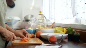 4k英尺长度 妇女的手与食谱书的切片蕃茄开放在前景,成份为烹调做准备在厨台 影视素材
