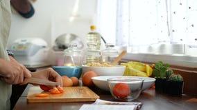 4k英尺长度 妇女的手与食谱书的切片蕃茄开放在前景,成份为烹调做准备在厨台 股票录像