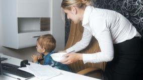 4k设法年轻女实业家的英尺长度坐与她的婴孩在办公室和喂养他用汤 股票录像