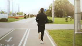 4K跑沿城市公园路的人 回到视图 在黑运动服,白色运动鞋的健身赛跑者 健康生活方式 影视素材