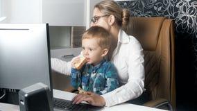4k运转在办公室的年轻女实业家录影,当她逗人喜爱的矮小的小孩儿子坐她膝部和吃时 股票视频