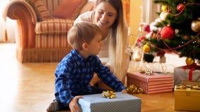 4k逗人喜爱的3年英尺长度oldd小孩男孩在早晨打开有母亲的圣诞礼物箱子 影视素材
