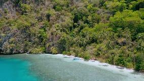 4k遥远的天堂海滩寄生虫鸟瞰图与摇摆在风的棕榈树的 在天蓝色的绿松石海的Banka小船 股票录像