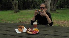 4k黑手工制造长的袖子坐在木乡下桌上的衬衣和绿色棕色太阳镜的美丽的女孩 影视素材