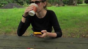 4k黑手工制造长的袖子坐在木乡下桌上的衬衣和绿色棕色太阳镜的美丽的女孩 股票录像