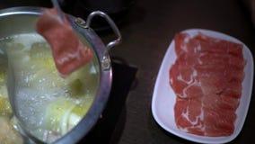 4K,使用筷子的亚裔妇女烹调的在中国hotpot汤的肉 股票录像