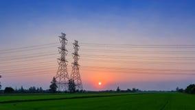 4K,时间间隔电杆、高压塔和天空日落和绿色米在前面调遣作为背景,天对夜,能量 股票录像