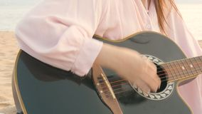 4K étroit de la longue femme de cheveux le jeu de la guitare acoustique à la plage avec le vent doux pendant le temps de coucher  clips vidéos