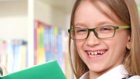 4K étudiant Child Reading Books dans la bibliothèque, portrait riant heureux d'écolière banque de vidéos
