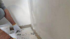 4K άτομο που χρωματίζει τους εσωτερικούς τοίχους στο επίπεδο που χρησιμοποιεί τη βούρτσα χρωμάτων Όμορφος νεαρός άνδρας που κάνει