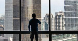 4k, ένας επιχειρηματίας που αγνοεί το αστικό επιχειρησιακό κτήριο από το παράθυρο απόθεμα βίντεο