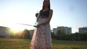 4k - Ένα όμορφο κορίτσι στο φόρεμα κάνει τις φυσαλίδες σαπουνιών στο στάδιο σε σε αργή κίνηση φιλμ μικρού μήκους