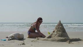 Ένα όμορφο κορίτσι σε ένα μαγιό σε μια εγκαταλειμμένη παραλία με ένα άσπρο σκυλί χτίζει ένα κάστρο άμμου από έναν θερινό θεριστή  απόθεμα βίντεο