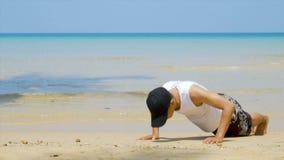 4K αθλητικό άτομο workout από την ώθηση επάνω στην αμμώδη παραλία, μέρος της διαγώνιας ικανότητάς του workout φιλμ μικρού μήκους