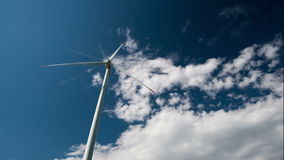 4k ανεμοστρόβιλος που παράγει την ηλεκτρική ενέργεια ενάντια στο μπλε ουρανό απόθεμα βίντεο