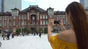 4K ασιατική γυναίκα που παίρνει το τηλέφωνο καμερών φωτογραφιών του σταθμού Marunouchi του Τόκιο απόθεμα βίντεο